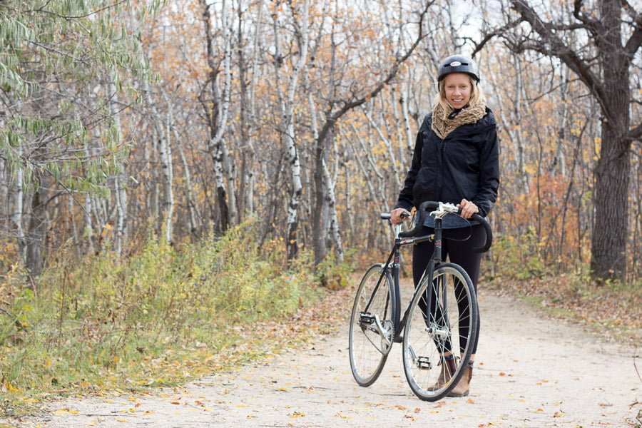 Jenna stands on the trail leading into the forest beside her bike, wearing a helmet.