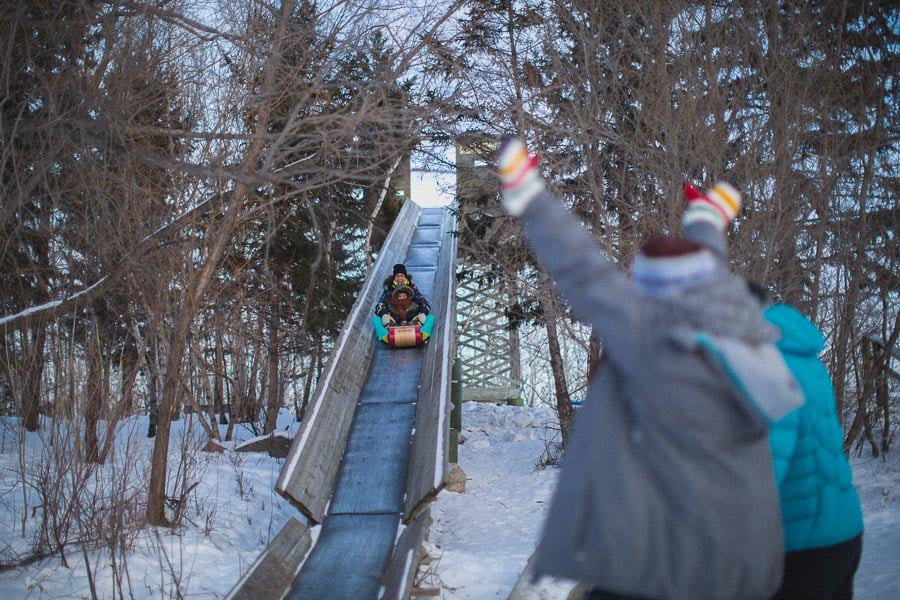 Friends waving to another sliding down the toboggan run