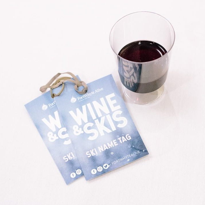 Picture of a glass of wine and two ski tags.
