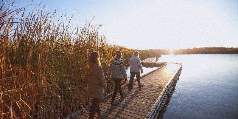 Group walking along the marsh boardwalk at FortWhyte Alive