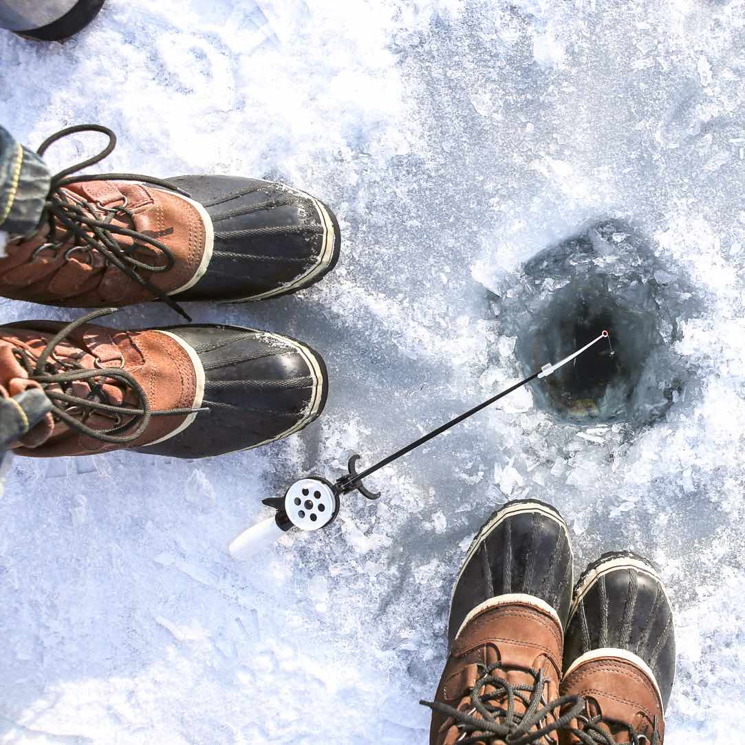 Standing over an ice fishing hole