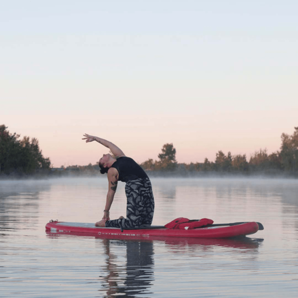 Ash Bourgeois practicing yoga on a standup paddleboard at FortWhyte Alive