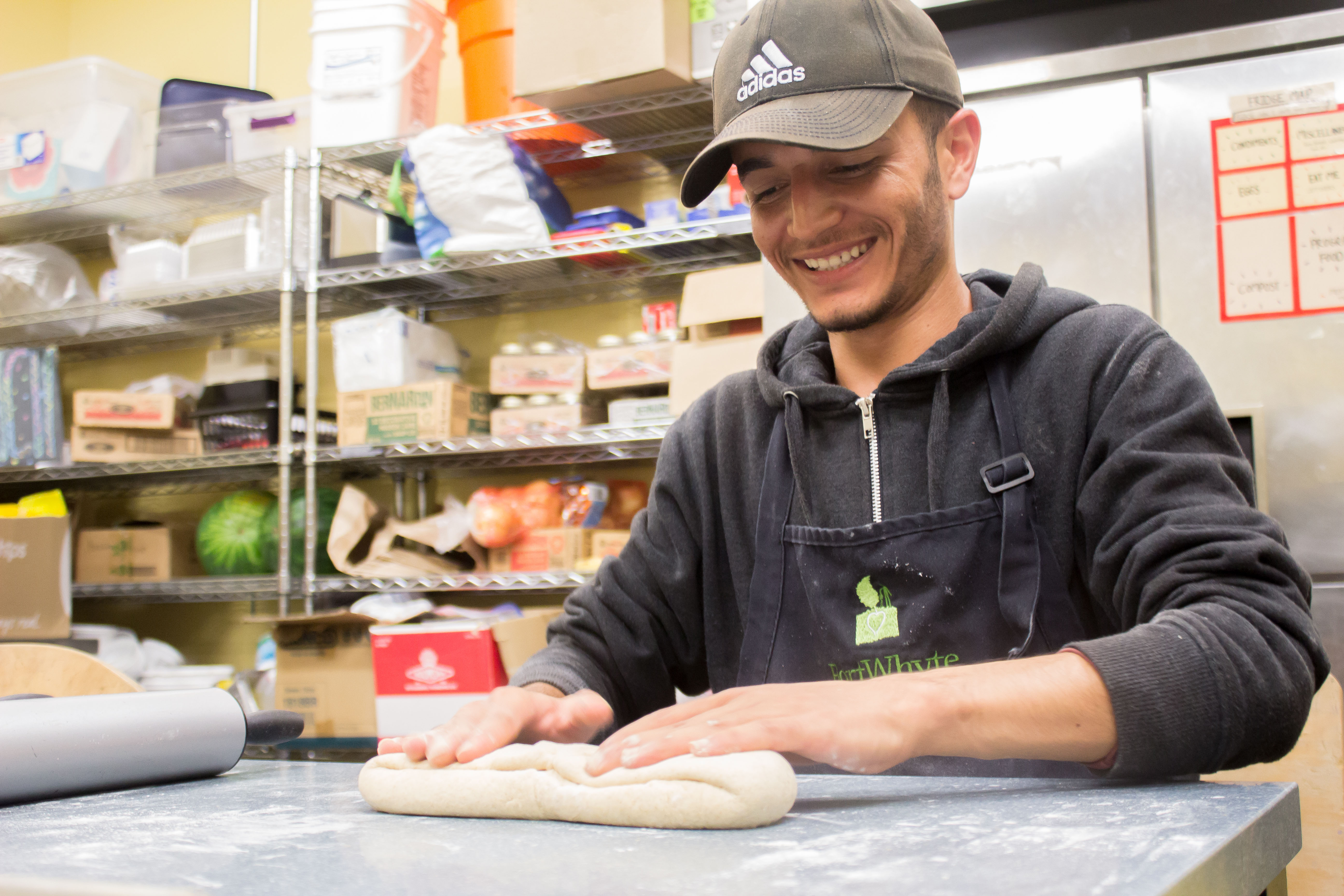 Junior staff rolling out pizza dough in the Farm kitchen.