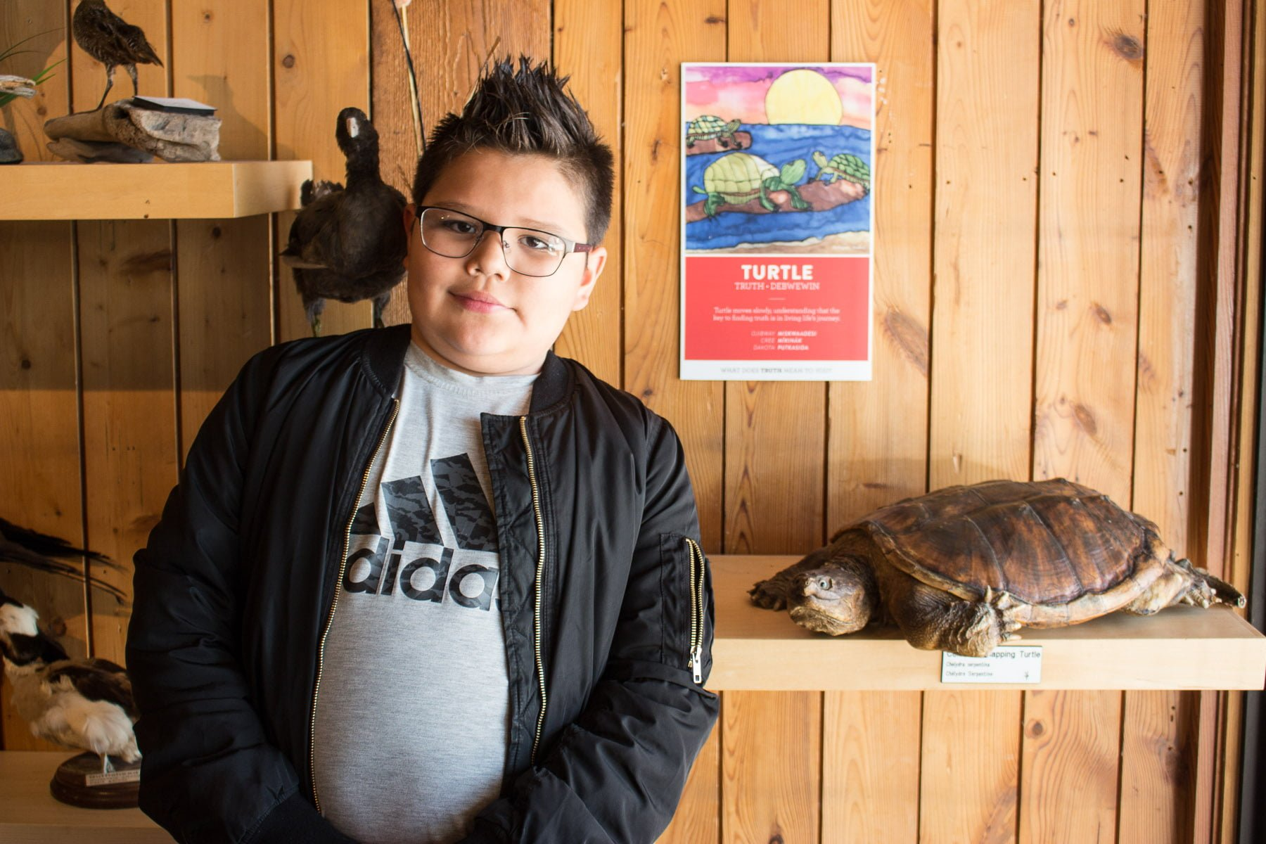 Student poses with his silkscreen of a turtle