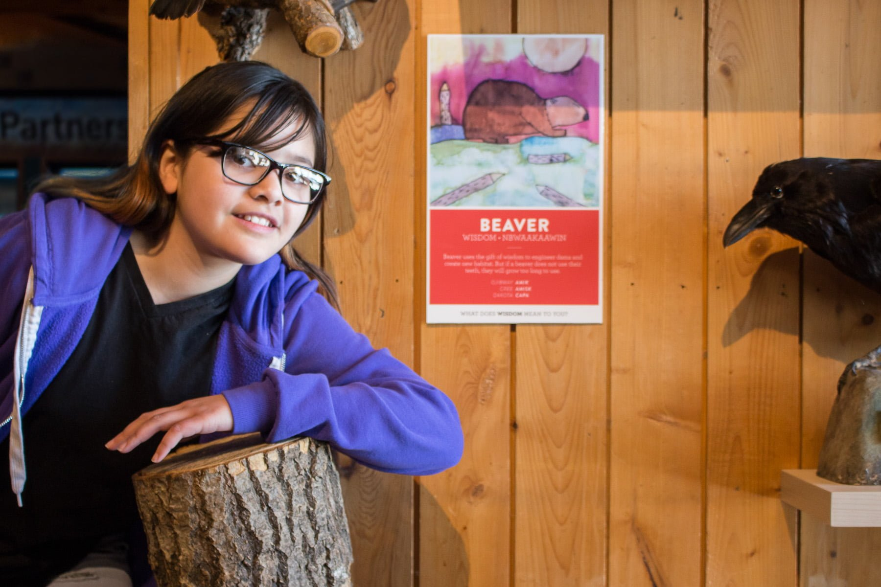 Student poses with her silkscreen of a beaver