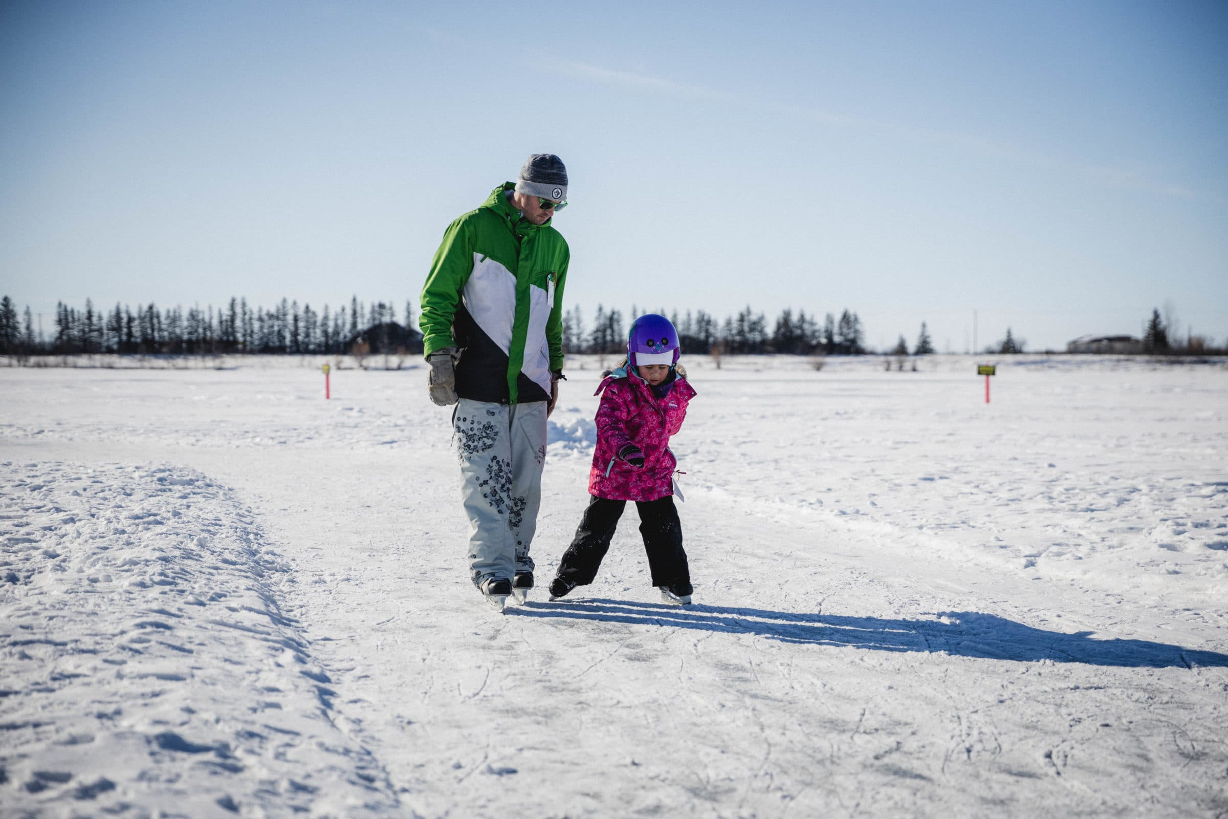 Adult teaching child to skate