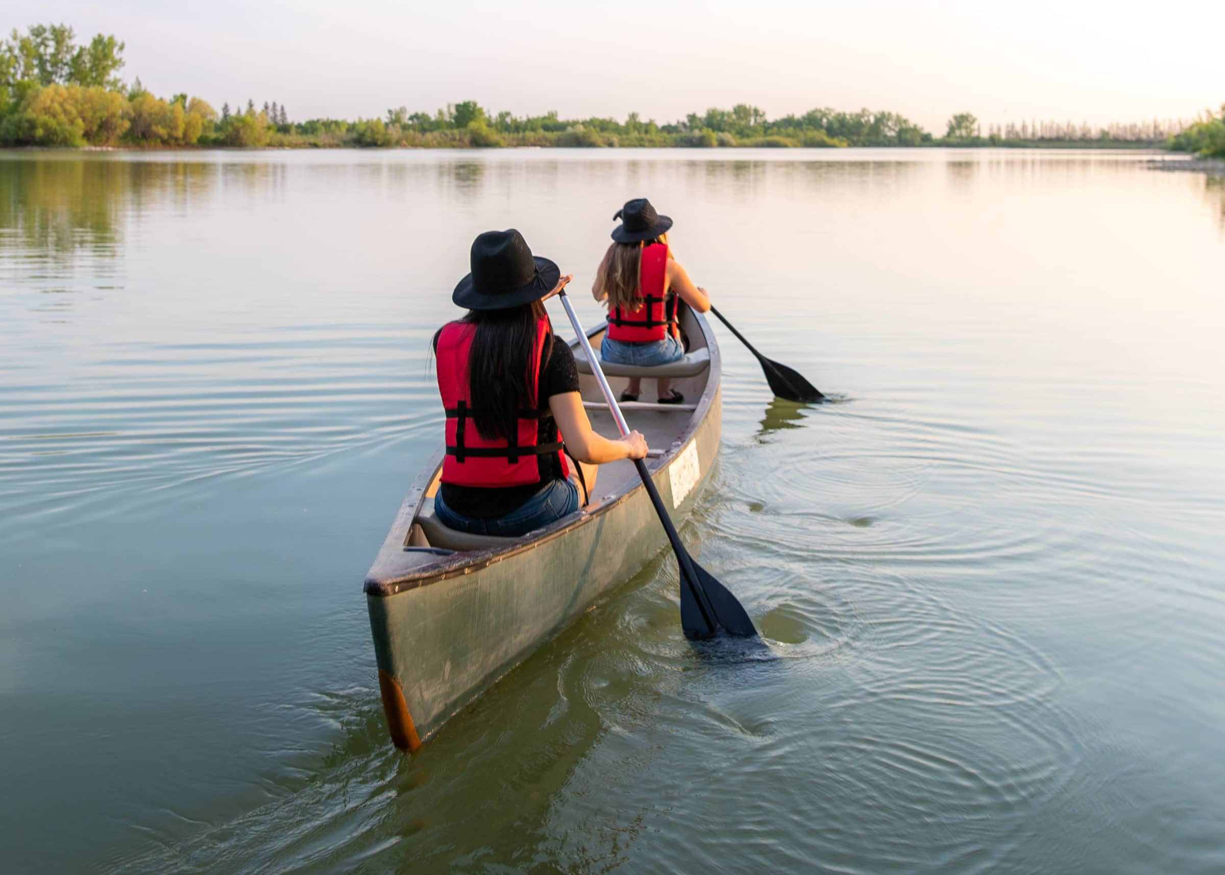 Two visitors paddle a canoe at FortWhyte Alive.
