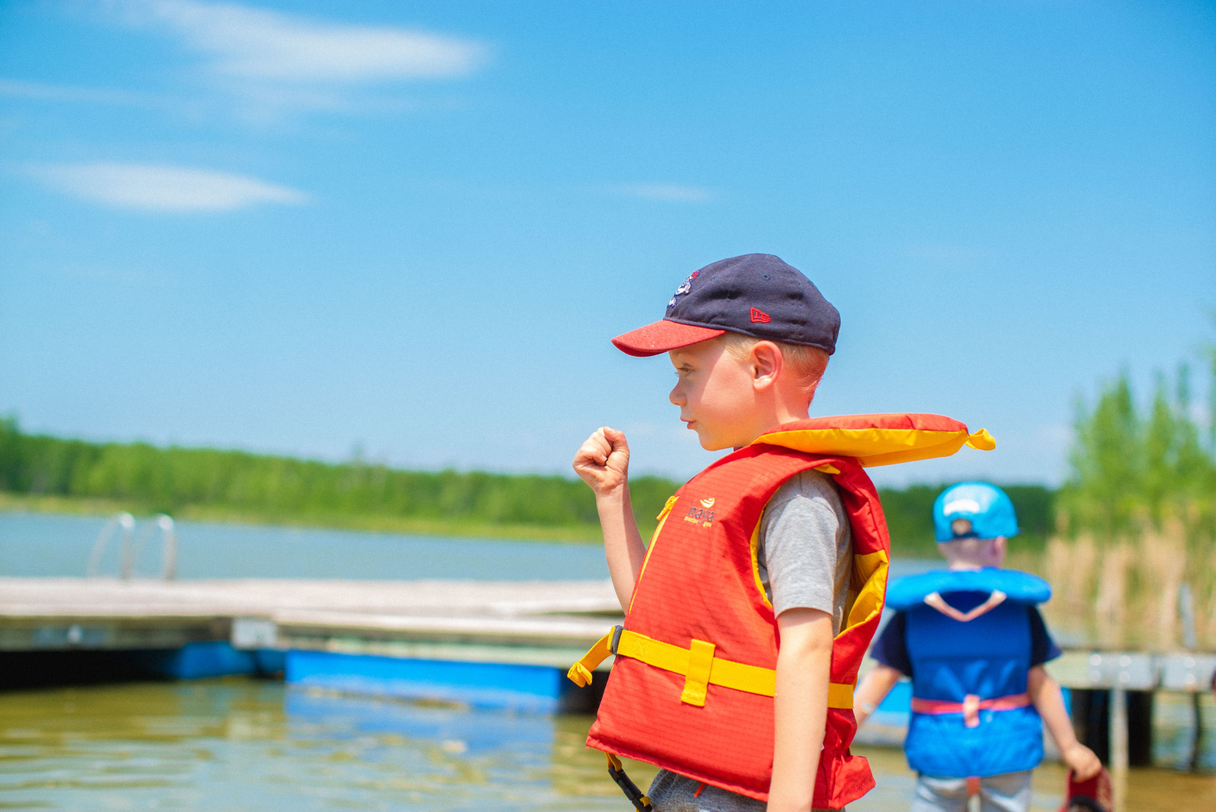Child wearing life jacket looks out over the lake in summer