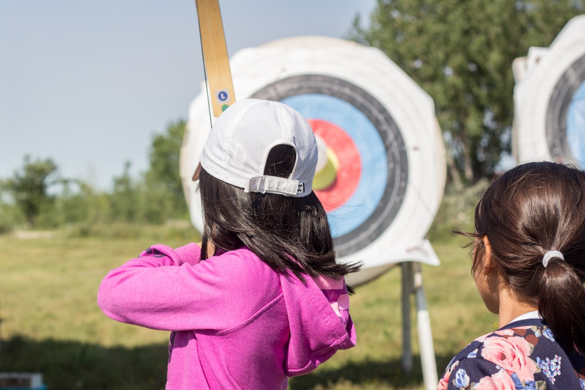 Young child setting up with her bow and arrow, facing a target