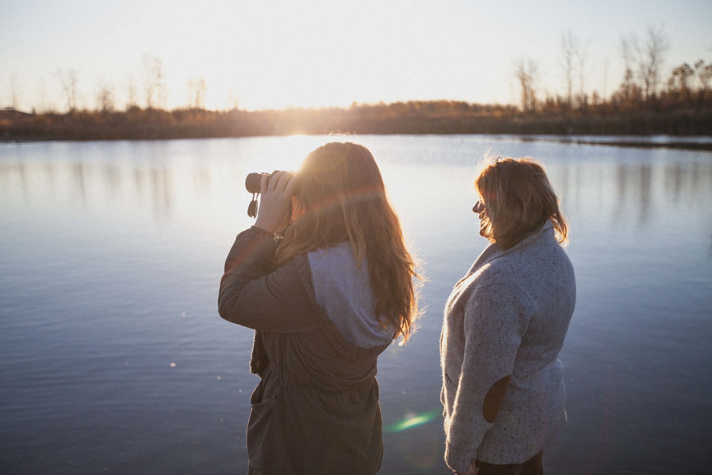 Two women using binoculars looking out to the lake.