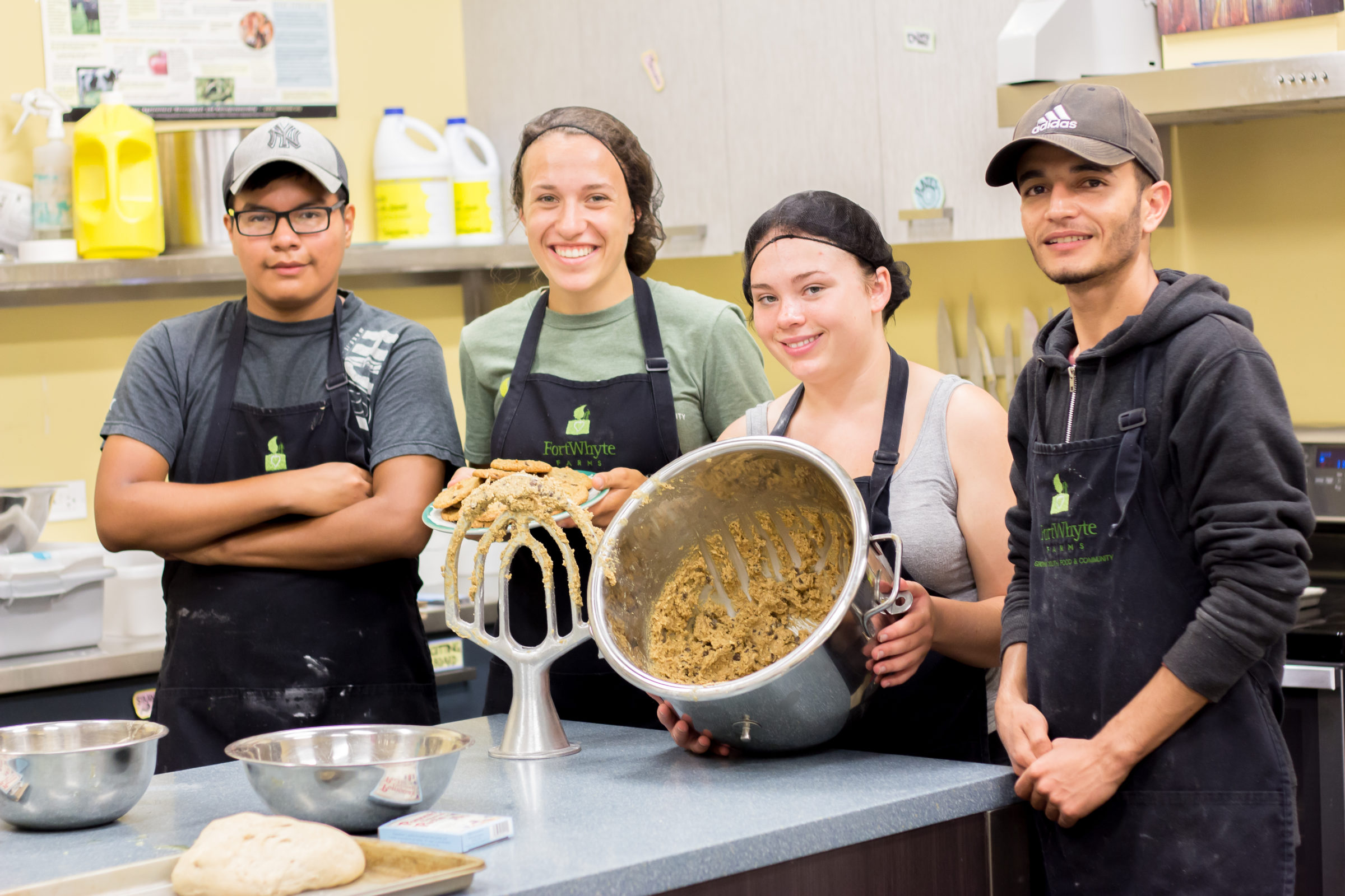 Four youth smiling as they cook in the FortWhyte Farms kitchen