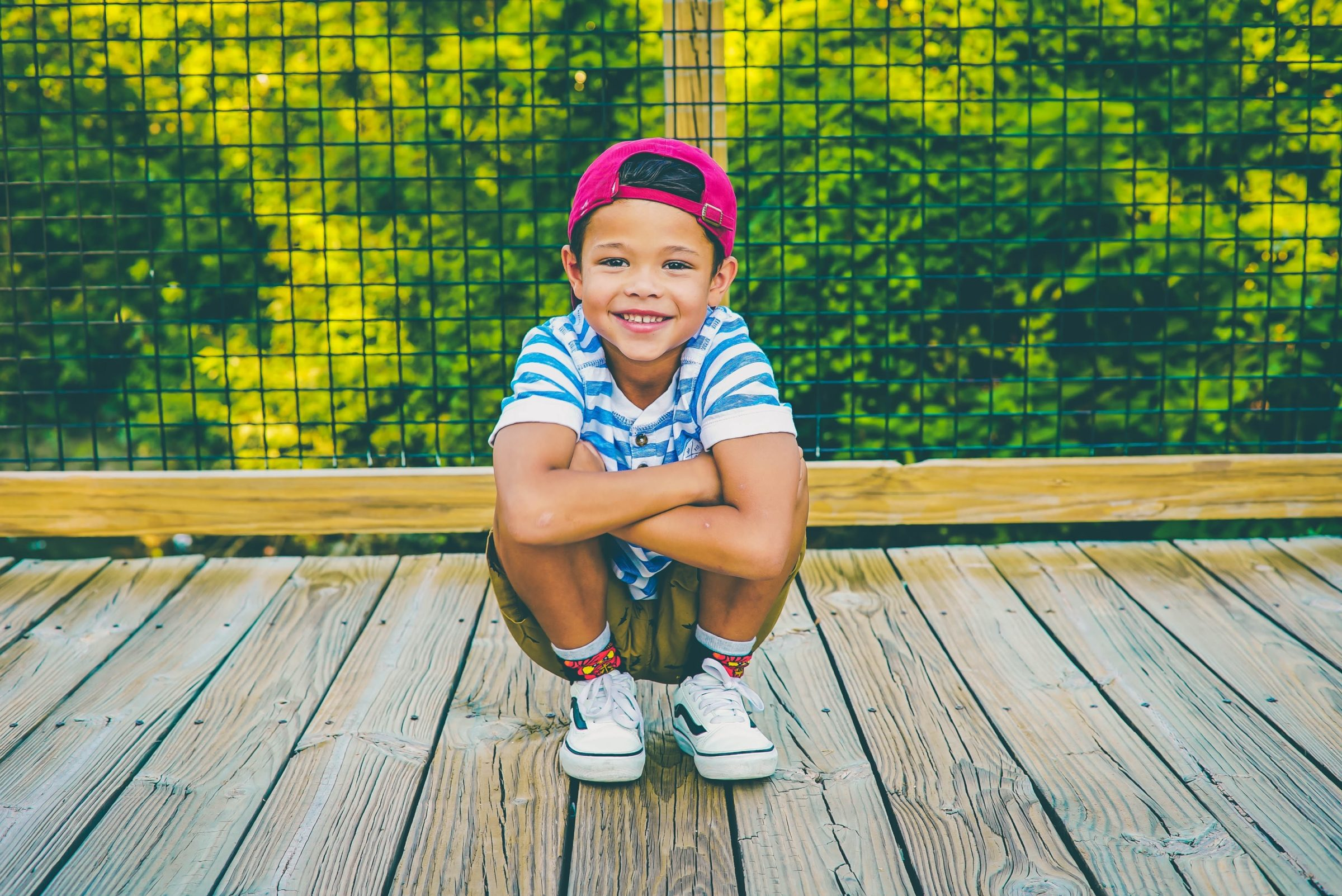 Young smiling child crouching on the boardwalk in summer