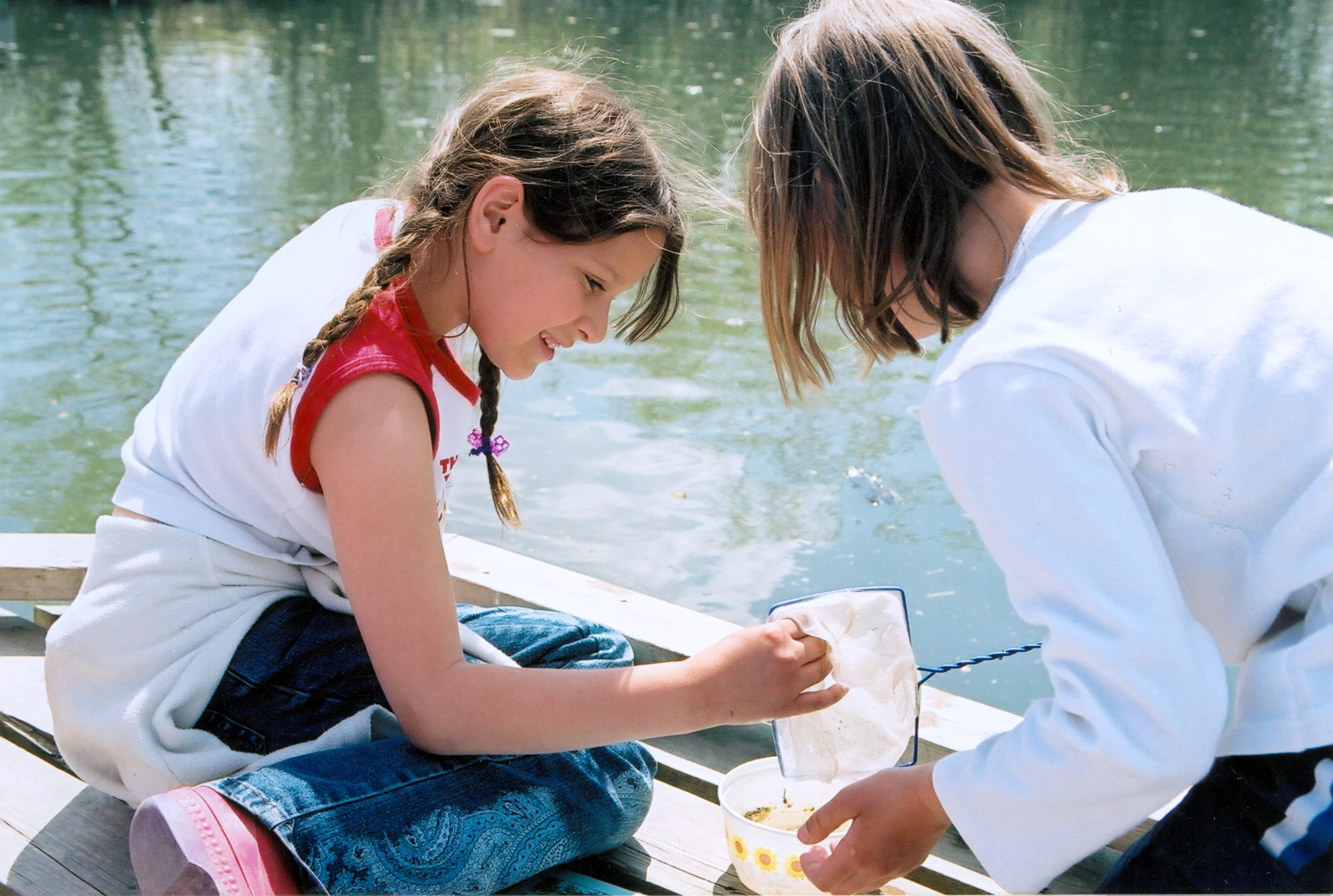 Two youth inspect their dipnet by the water in summer