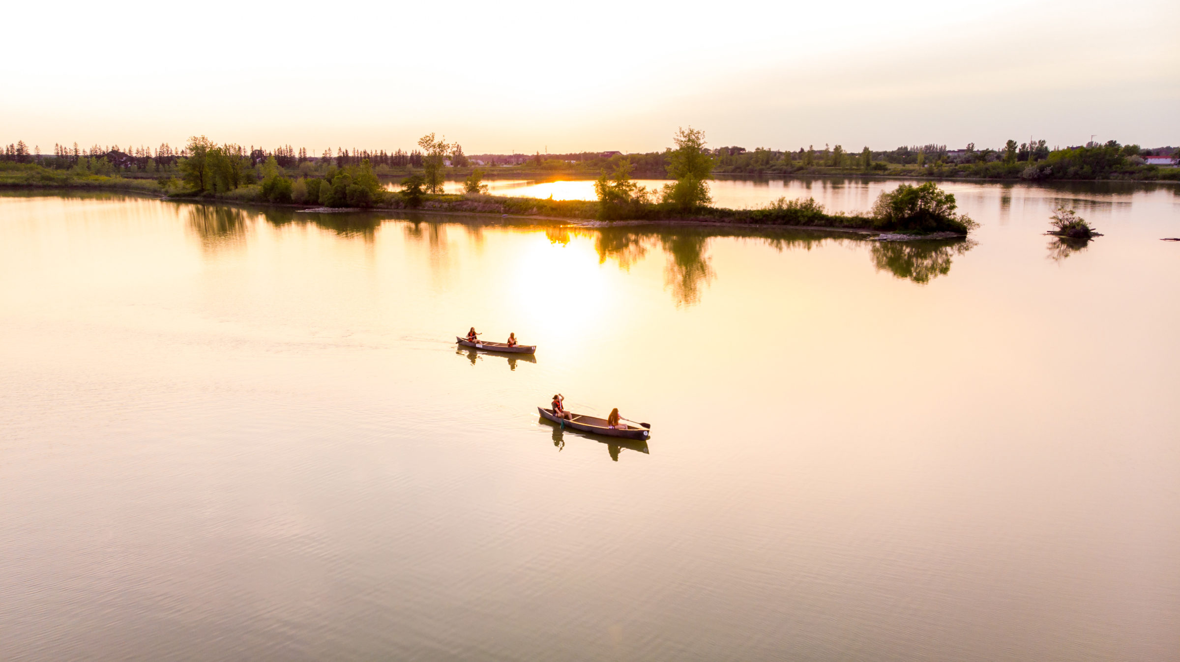 Two canoes padding at FortWhyte Alive at sunset.