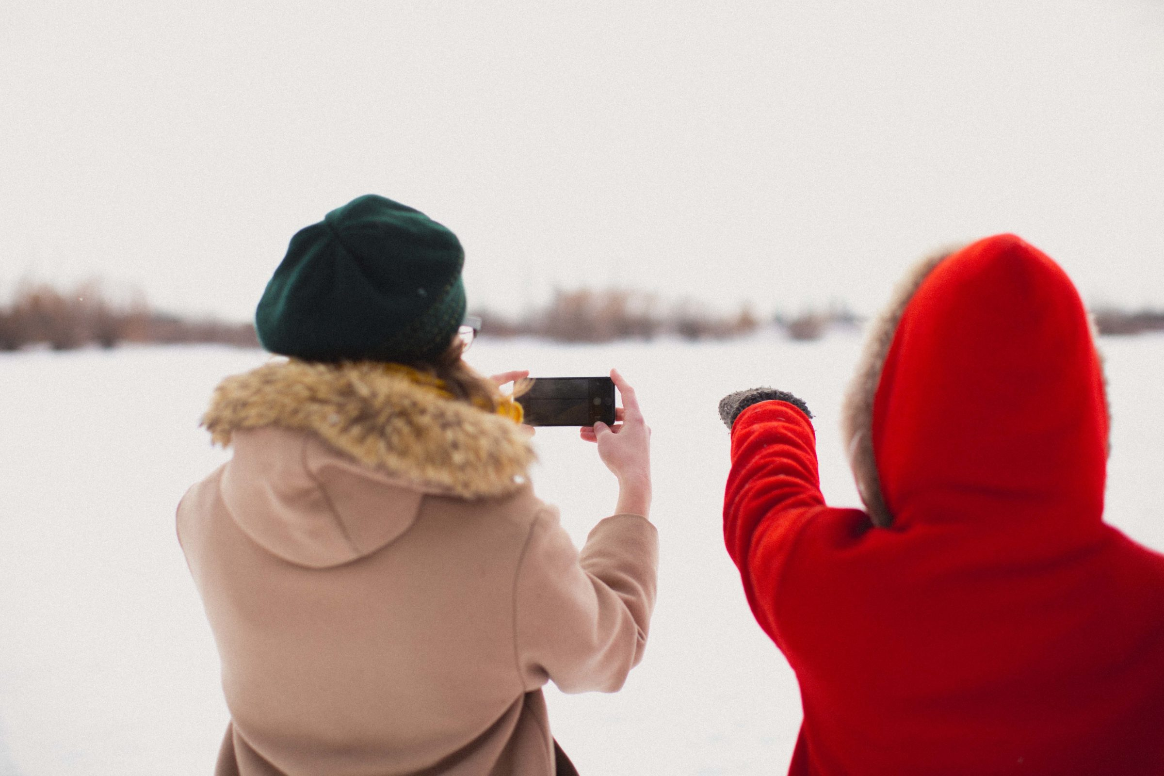 Two adults look out into an open snowy field, one holding their phone to take a picture while the other points out at something.