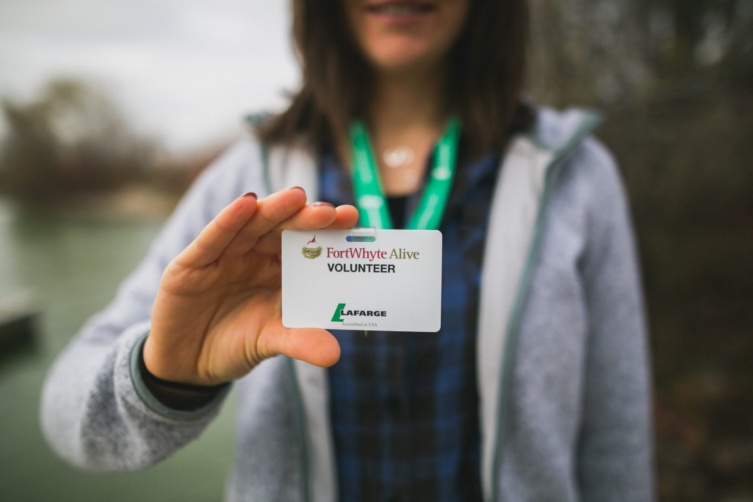 Woman holding FortWhyte Volunteer name tag
