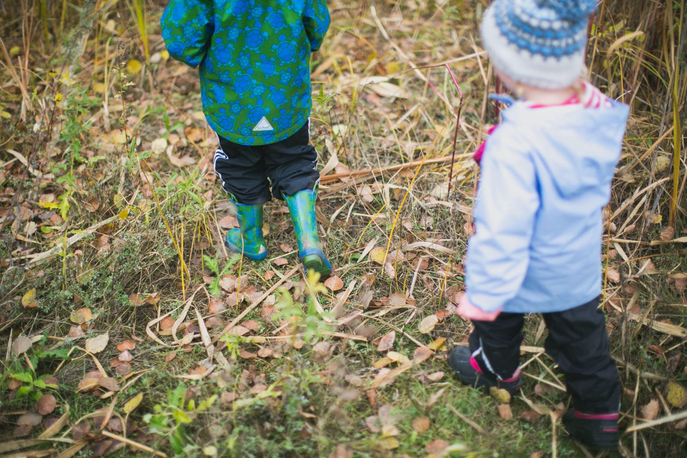 Children walking in rubber boots in autumn.