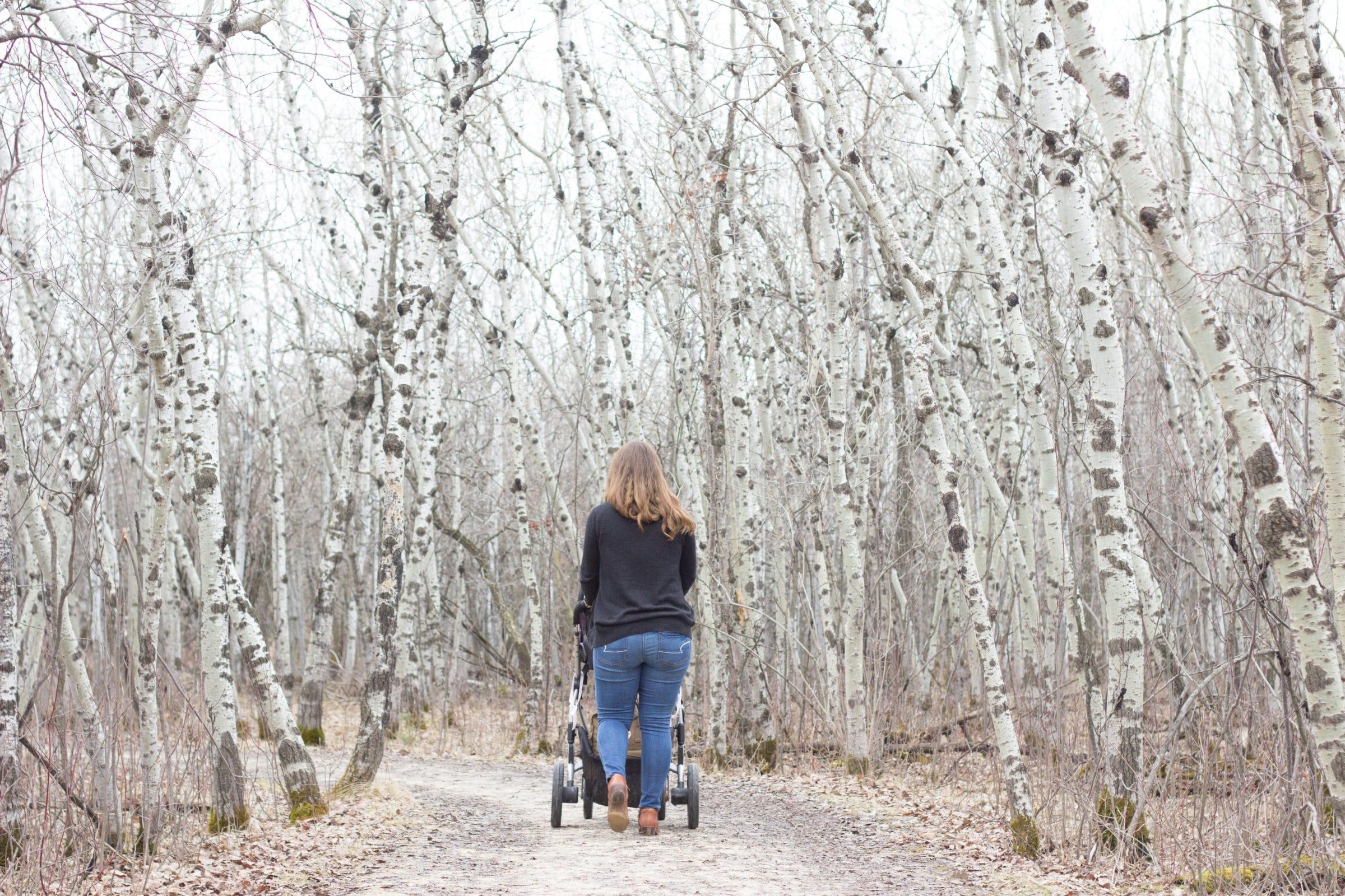 Woman pushing stroller down path in autumn