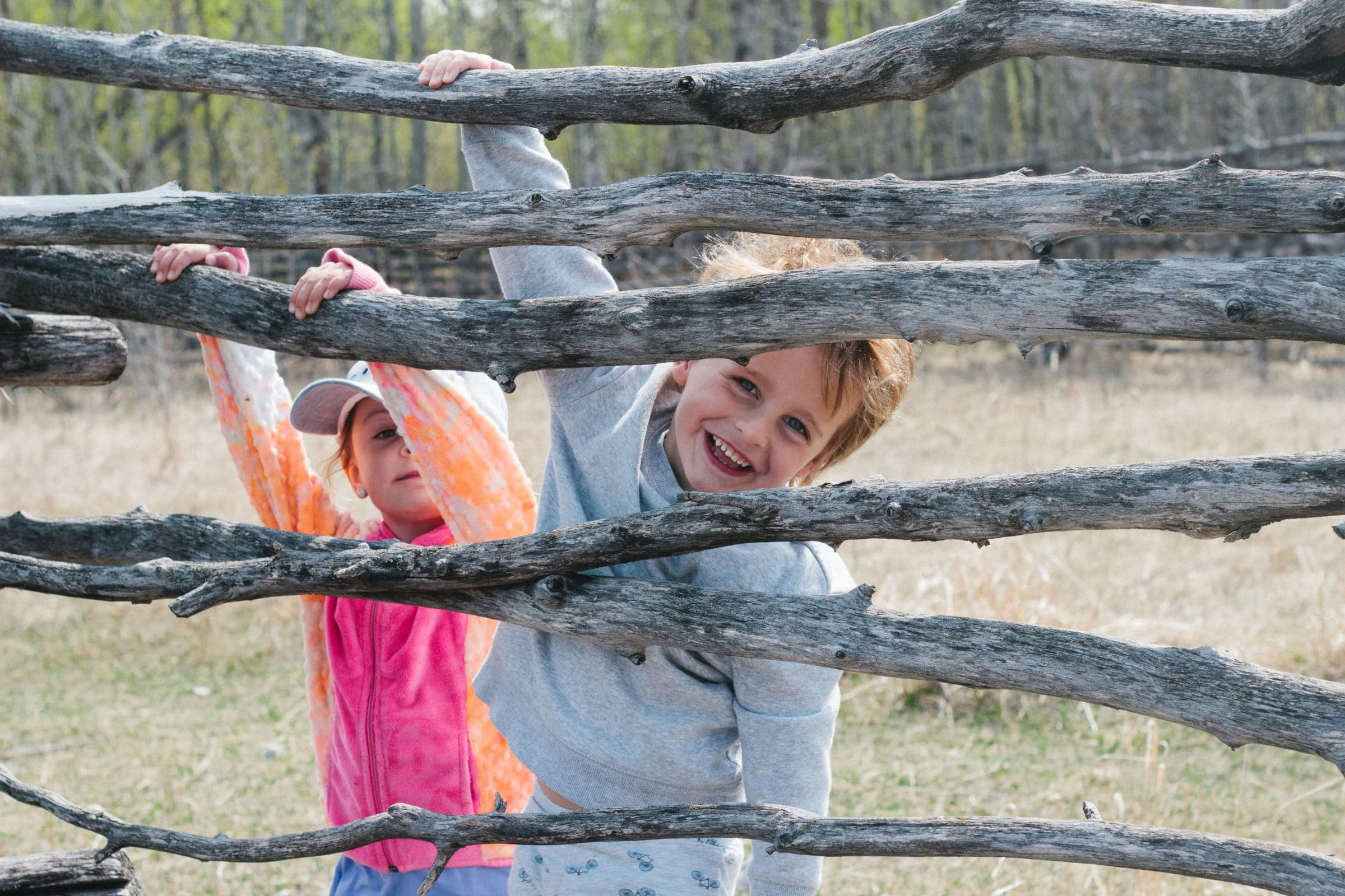 Two children smiling through wooden fence.
