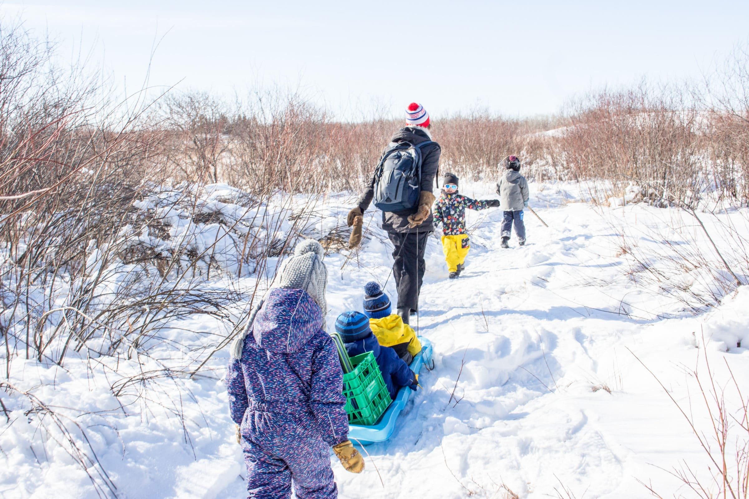 Adult pulling child in sled with other children walking in front and behind