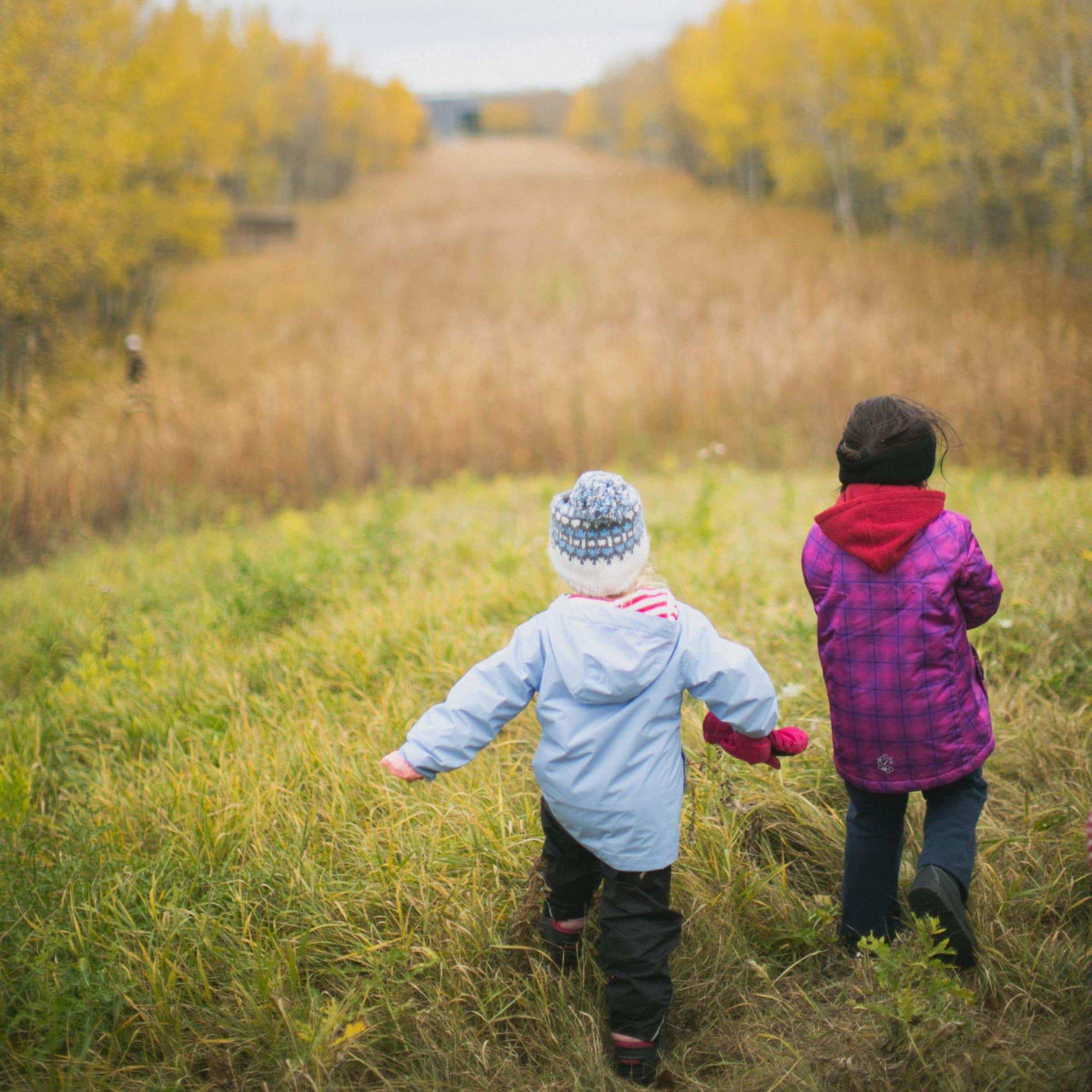 two bundled children frolic through tall grass