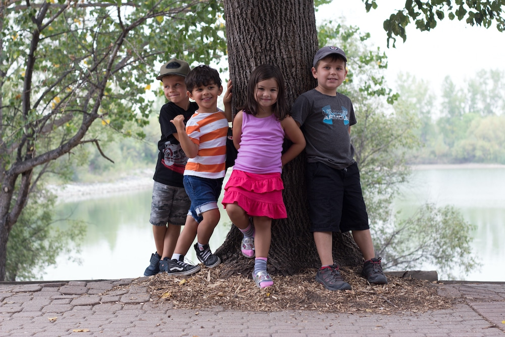Four children smiling and leaning up against a tree in summer