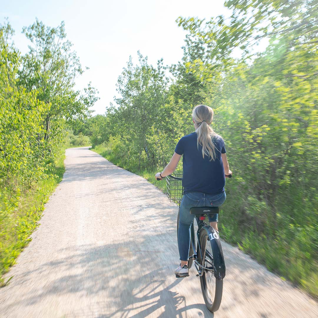 Visitor biking on the trail in summer