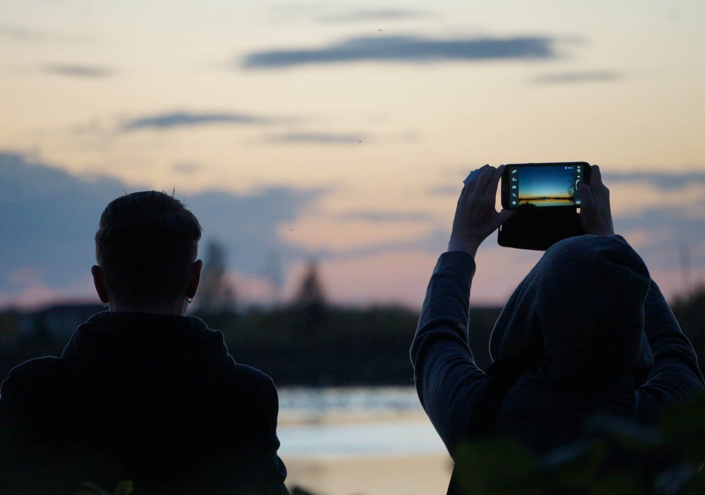 Two visitors take a photo of the sunset in summer.