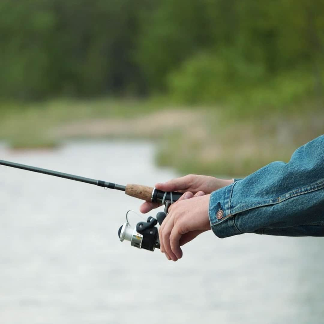 Hands holding fishing rod with water in the background.