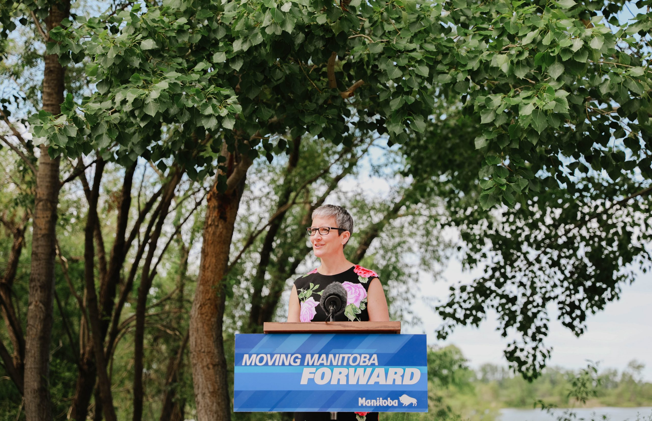 Liz Wilson stands at podium with greenery behind her