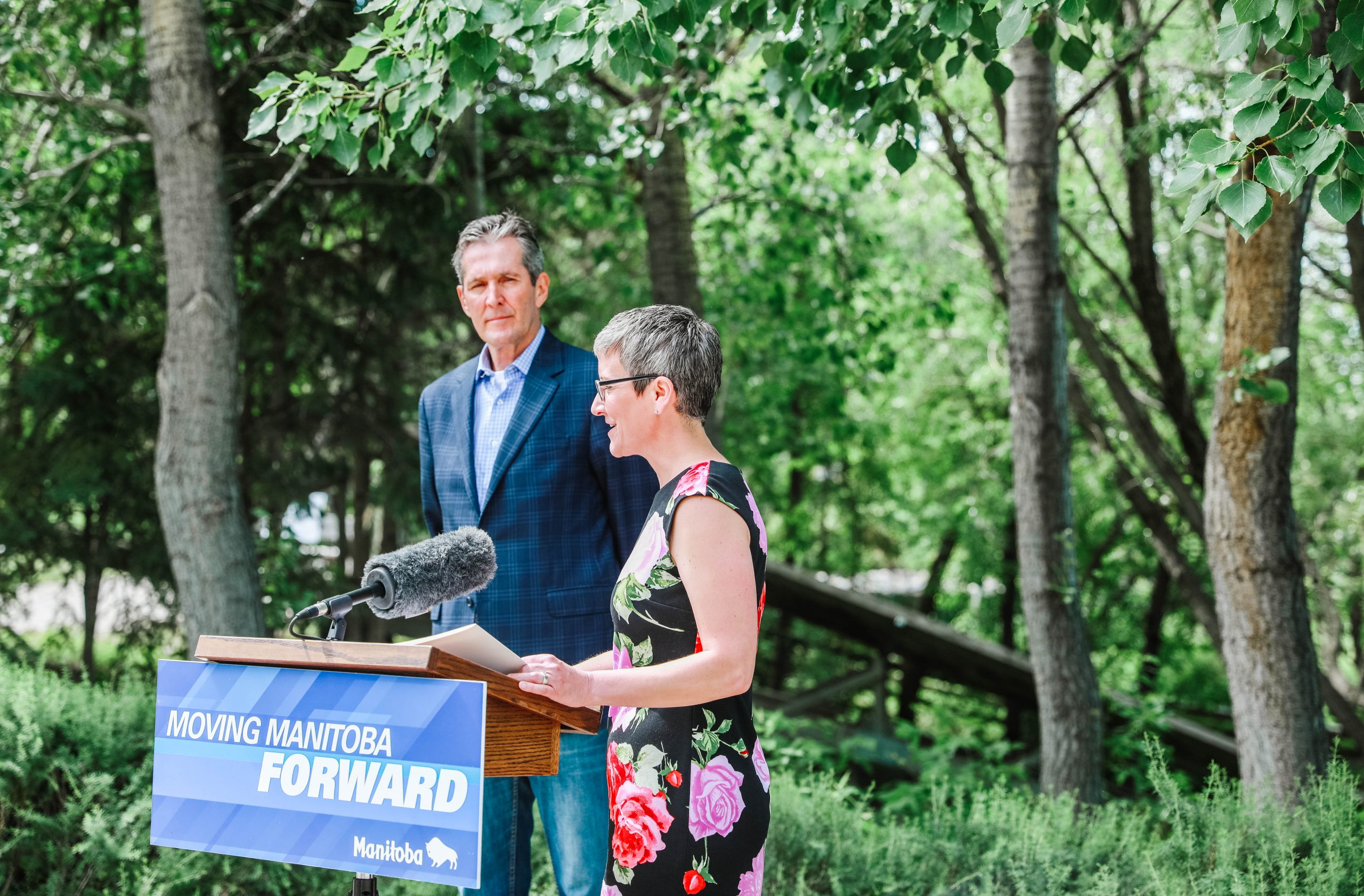 Liz Wilson and Brian Pallister stand behind podium at FortWhyte