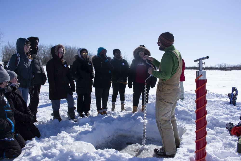 A group of high school students listen to a presenter outdoors in winter