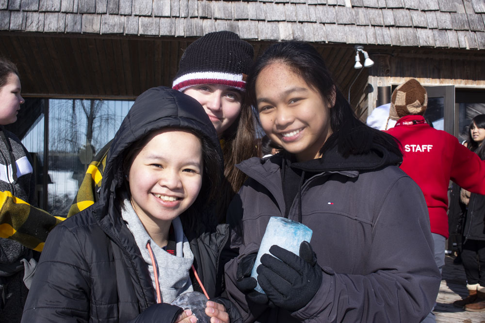 Three high school students hold up a block of ice