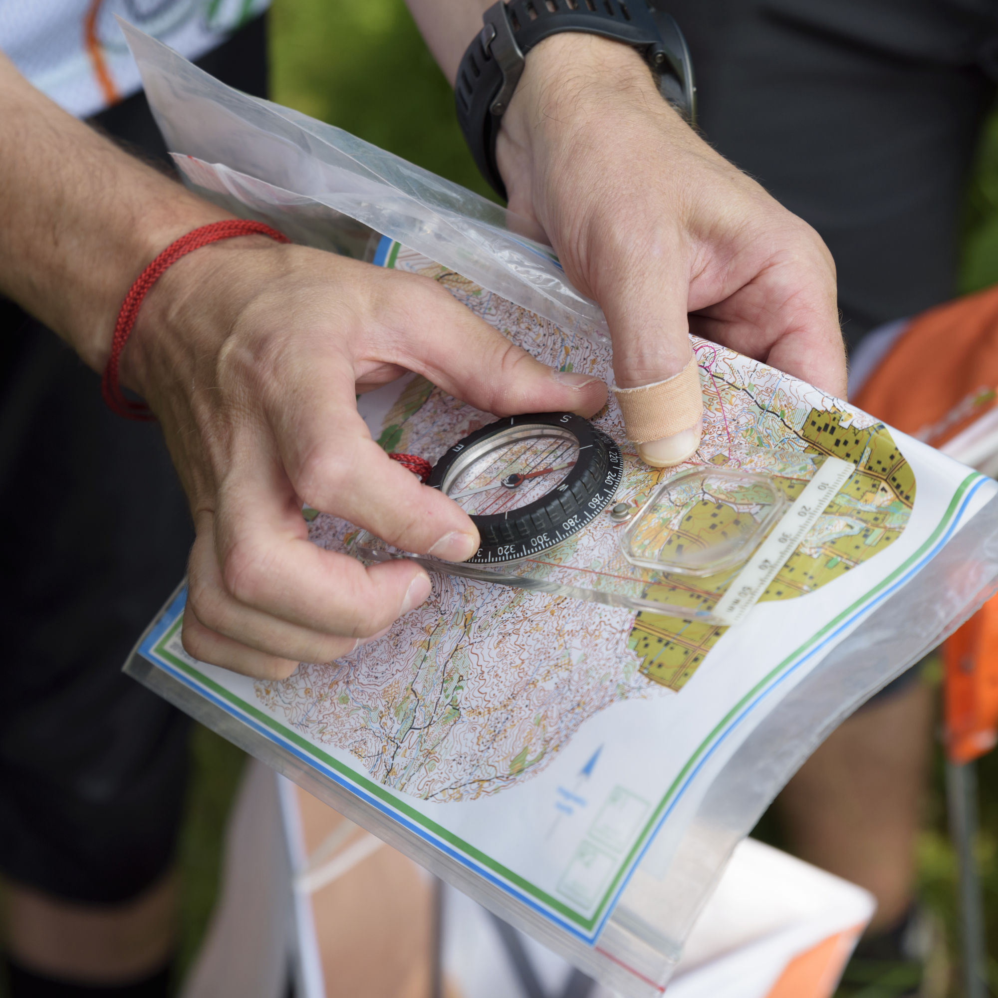A hand holds a compass overtop of a paper map