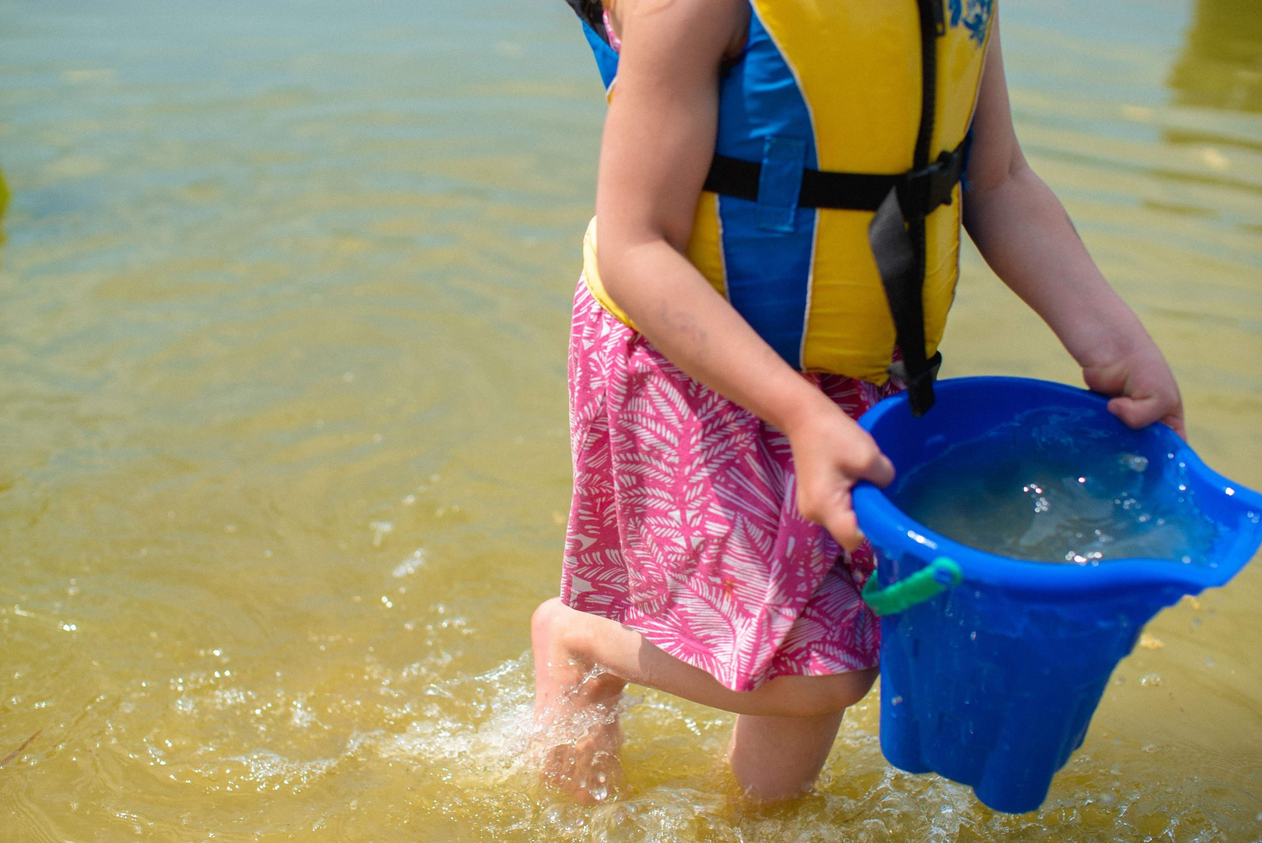 Child runs in a lake holding a blue bucket of water