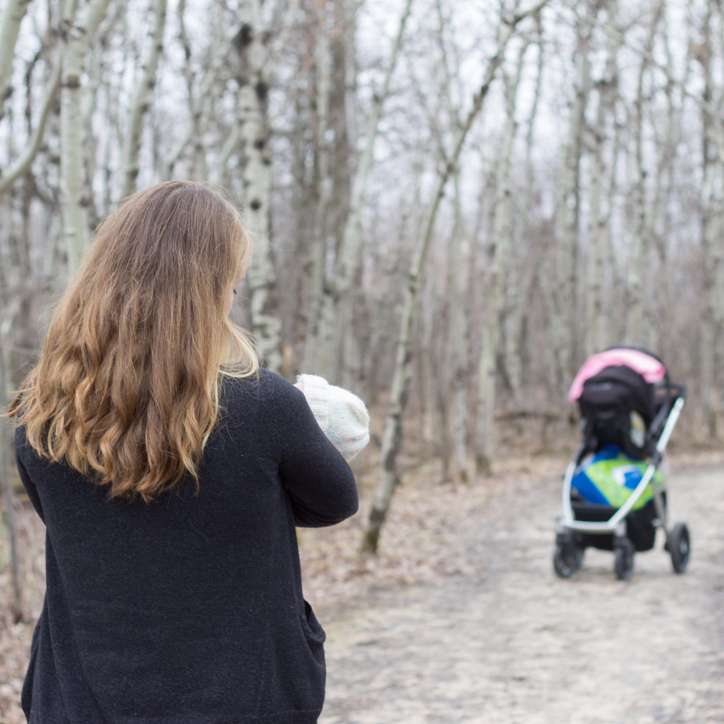 An adult hold their baby in their arms. They stand in a fall forest bare of leaves.