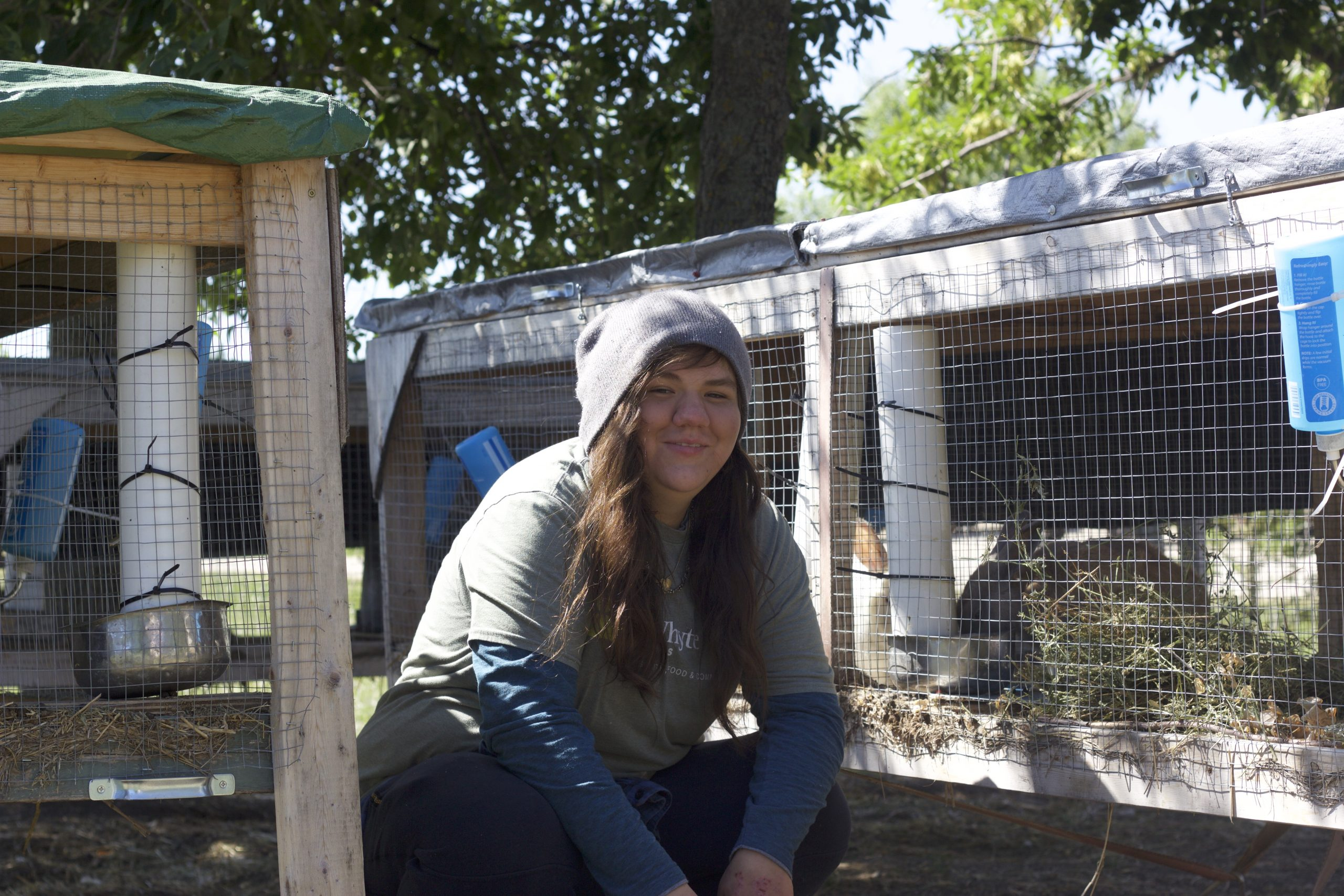 Sara from FortWhyte Farms kneels next to the rabbit enclosure.