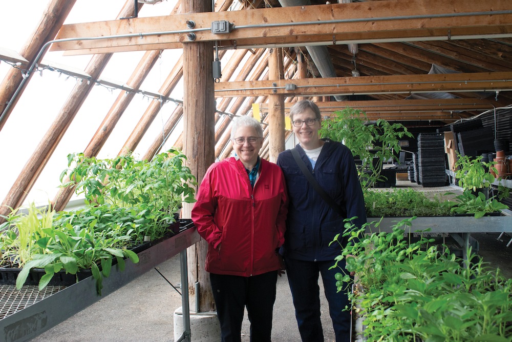 Pam and Kathy stand side by side smiling in the FortWhyte Farms greenhouse