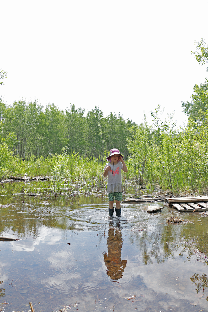 Tessa stands in a puddle wearing a pink hat and rubber boots