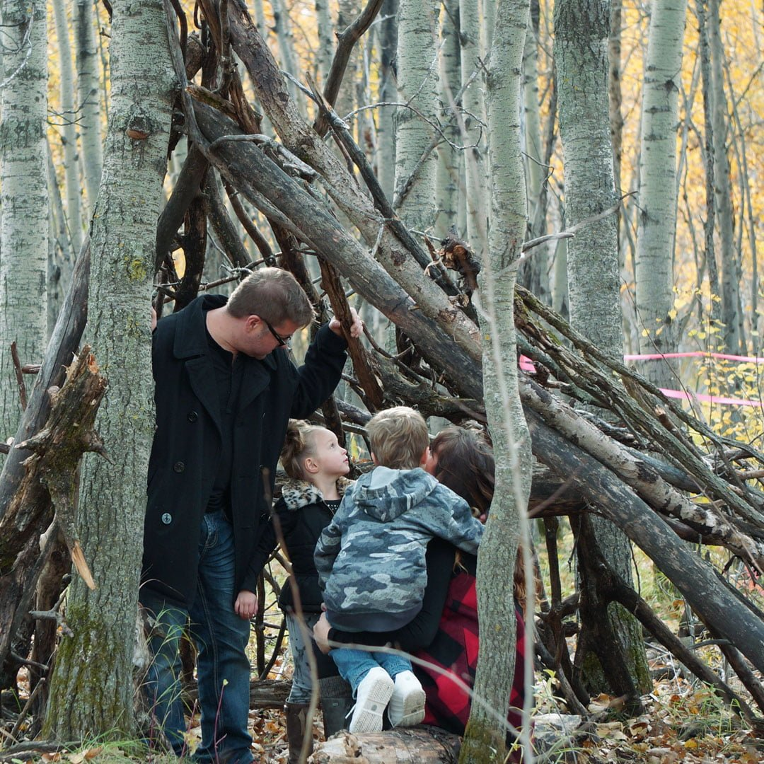 A family huddles under a makeshift tipi made of logs