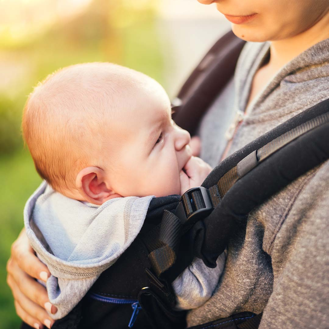 A parent wears her baby in a carrier on her chest
