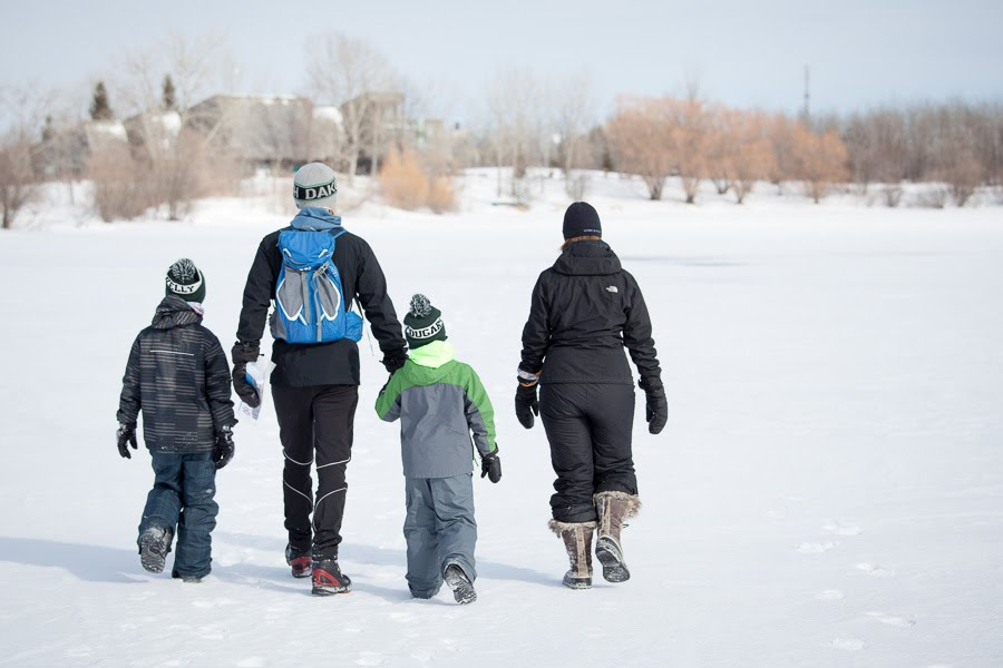 Two adults and two children are dressed in snow gear and walking out into the open field covered in snow.