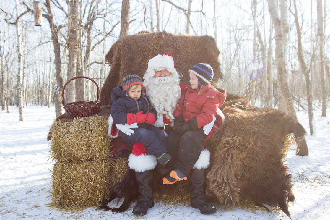Two children sit on Santa's lap, all together on a large chair made of stacked hay bales