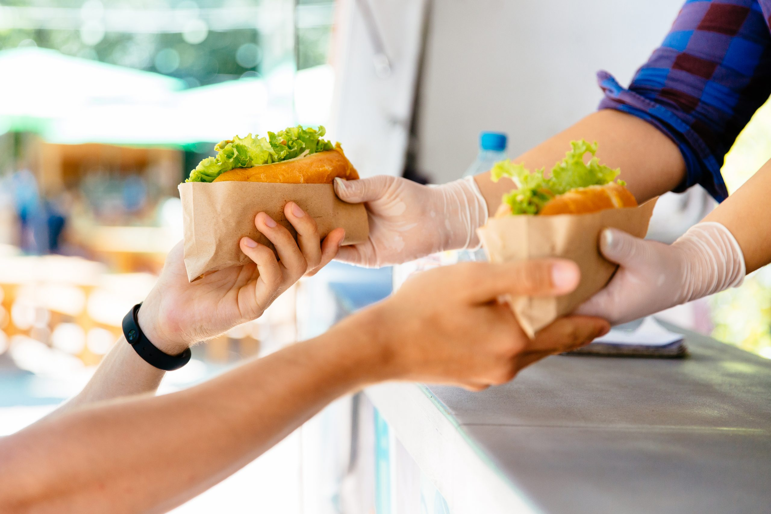 Two sets of hands hold two hot dogs filled with lettuce.