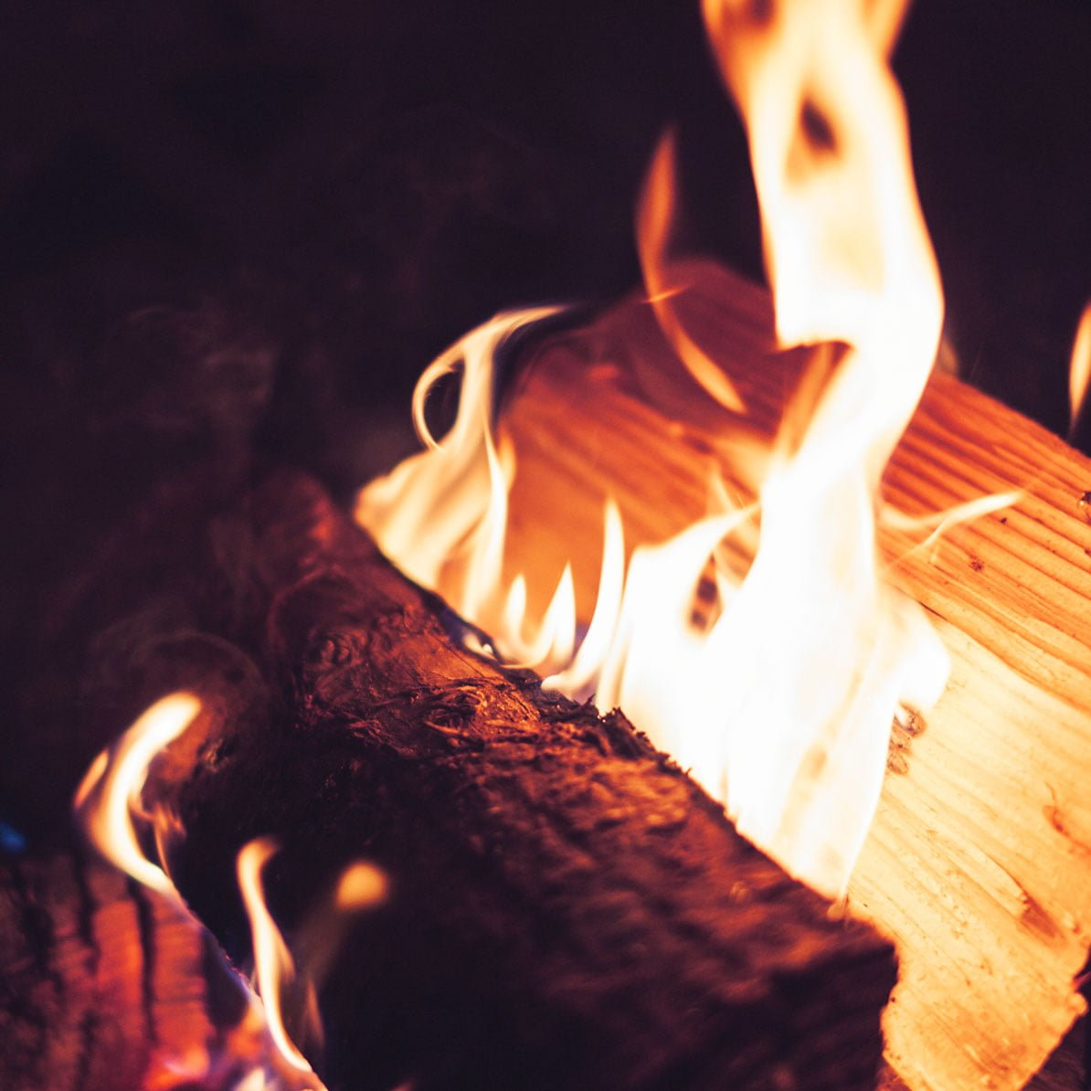 A large yellow flame lights a log