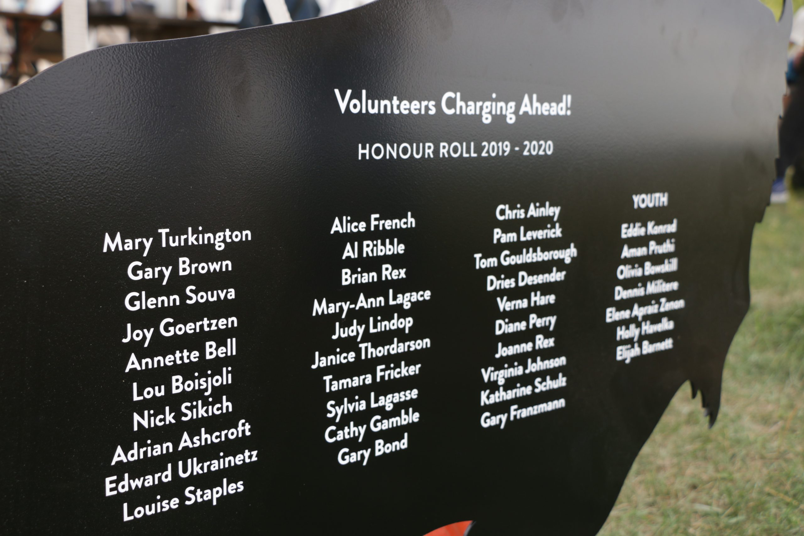 Columns of names are listed on a black buffalo shaped piece of metal, titled Volunteers Charging Ahead! 2019-2020 Honour Roll