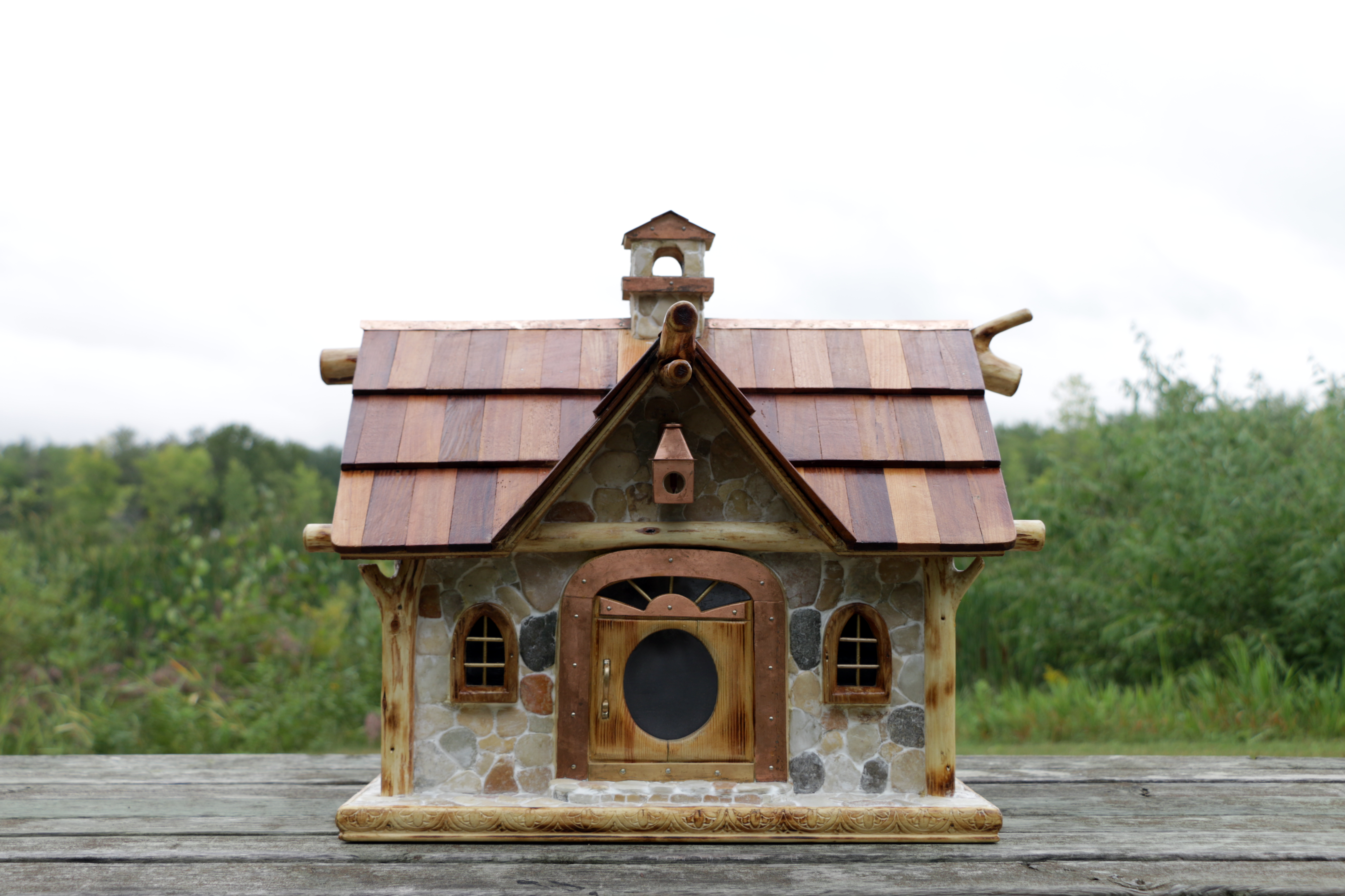Hand crafted bird feeder resembling a house.
