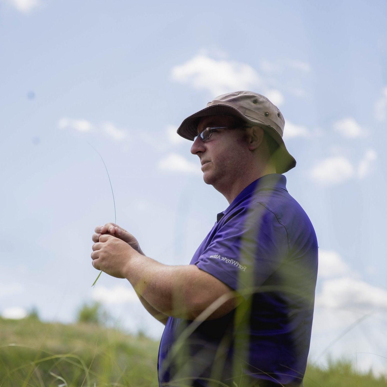 A FortWhyte Educator holds a blade of grass outside and speaks to an unseen crowd of people.