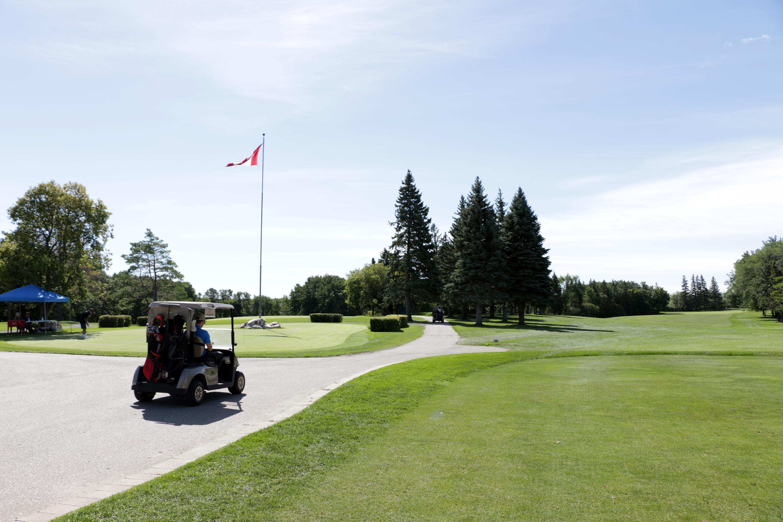 A golf cart drives down the path between lush green grass.