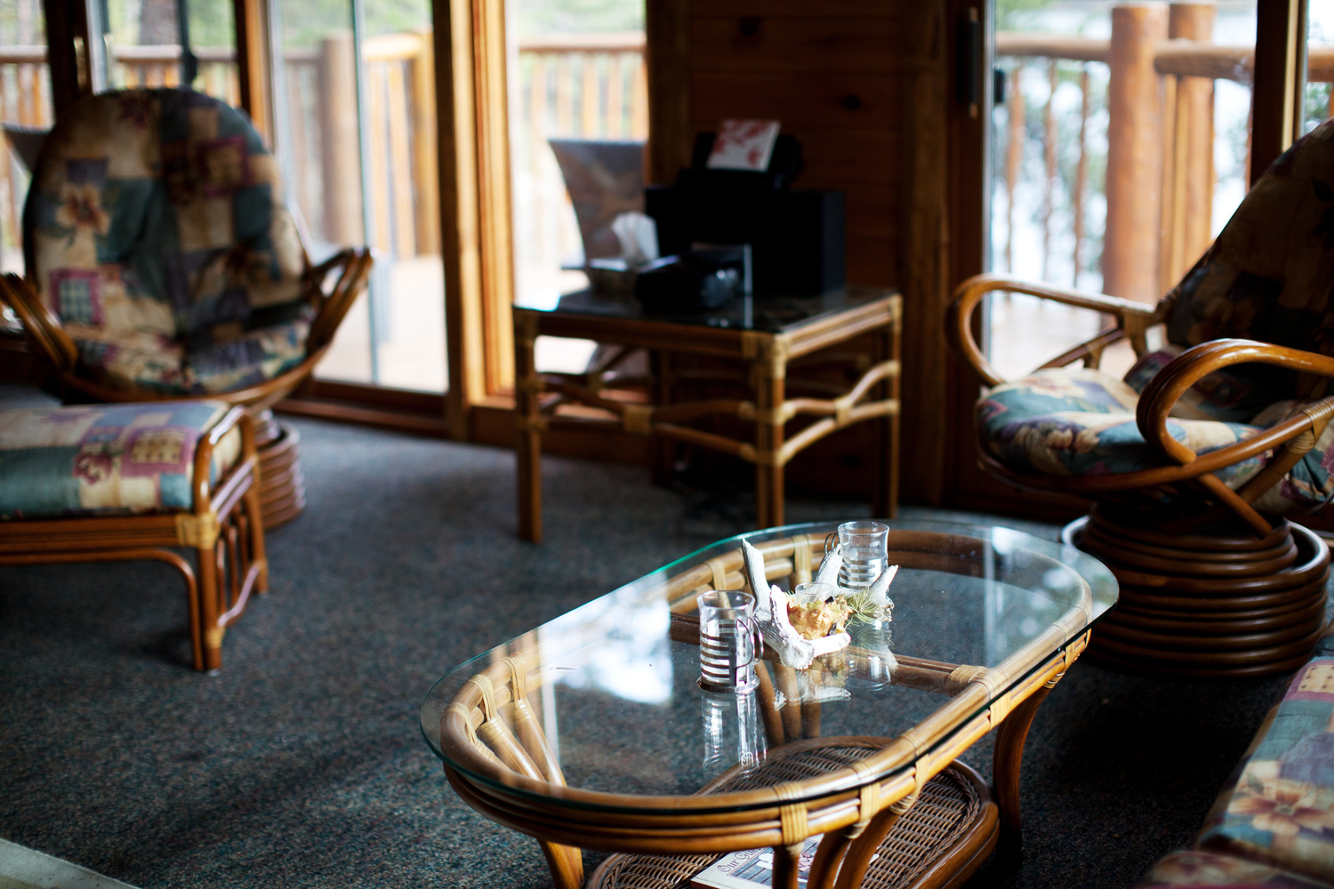Interior of the cabin livingroom, glass table a cushioned chairs.